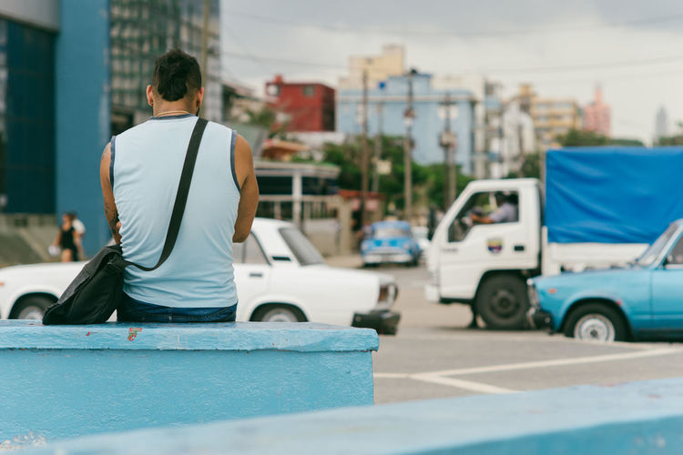 Havana~ Architecture Blue Building Exterior Built Structure Casual Clothing City Day Land Vehicle Leisure Activity Lifestyles Men Mode Of Transportation One Person Outdoors Real People Rear View Sitting Street Transportation