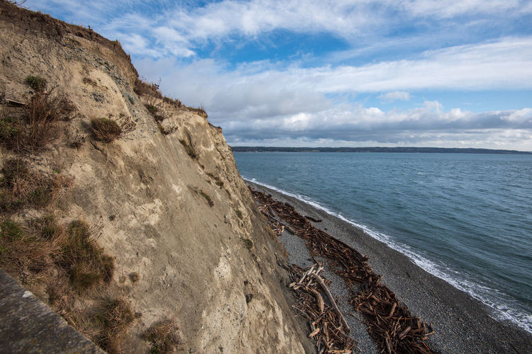 Scenic view of cliff, sea against sky