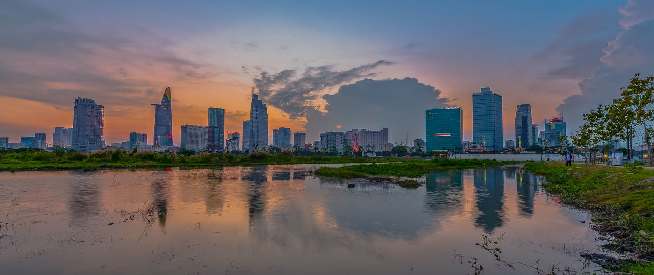 Sai Gon By Night, Ho Chi Minh City Sai Gon City Sai Gon River Architecture Building Exterior Built Structure By Night City Cityscape Cloud - Sky Day Downtown District Modern No People Outdoors Reflection Sky Skyscraper Sunset Tall - High Travel Destinations Urban Skyline Water Waterfront Perspectives On Nature Stories From The City The Architect - 2018 EyeEm Awards