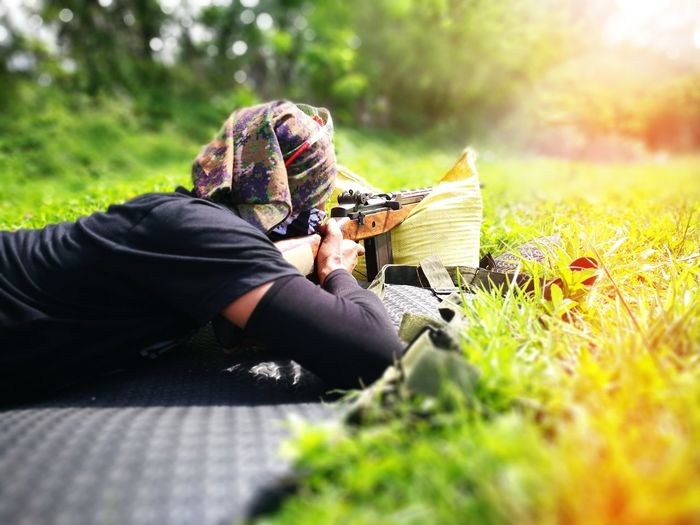 Man shooting rifle while lying on grass outdoors