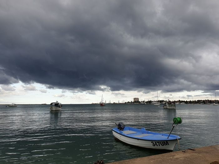Boats moored in sea against storm clouds