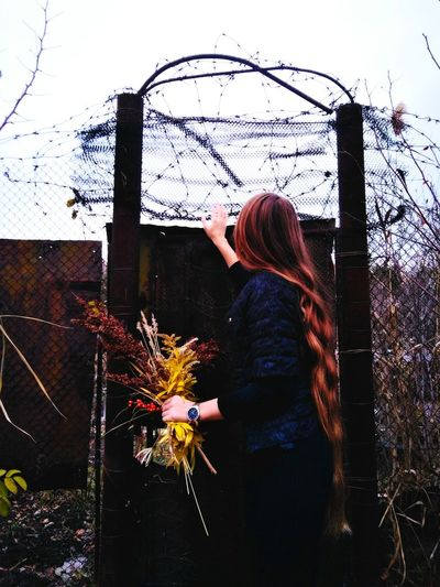 Young Woman Standing By Fence