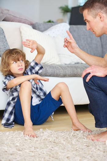 Father scolding son sitting by sofa at home