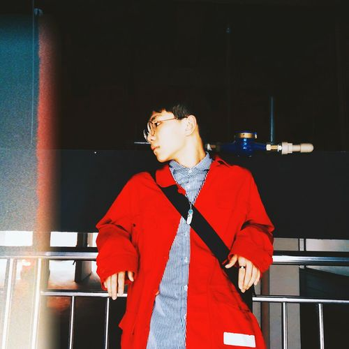 Low Angle View Man Of Wearing Red Coat Leaning On Railing