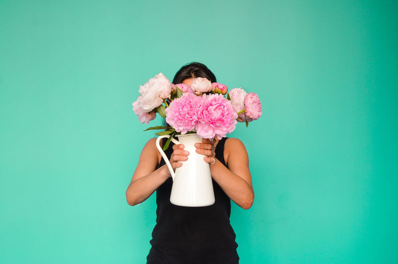 Woman Holding Flower Vase While Standing Against Green Background