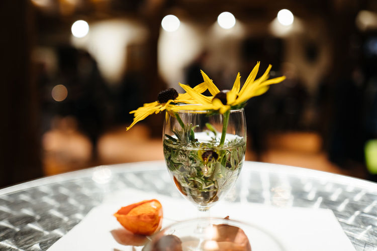 Yellow flowers in wineglass on table