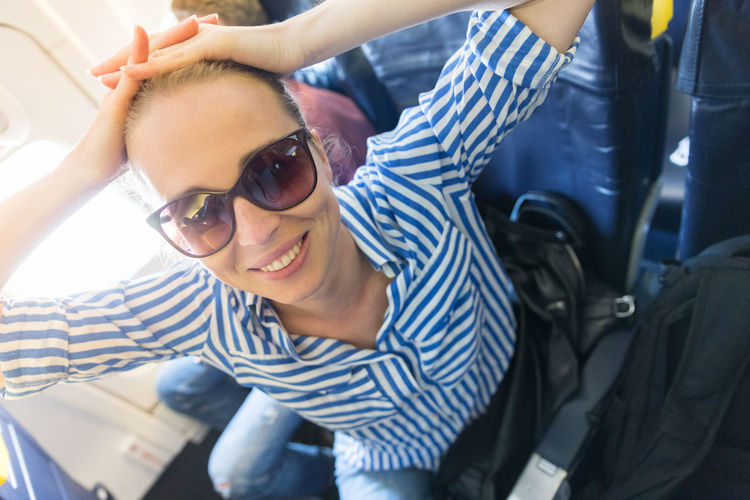 Portrait of smiling woman wearing sunglasses sitting at airplane