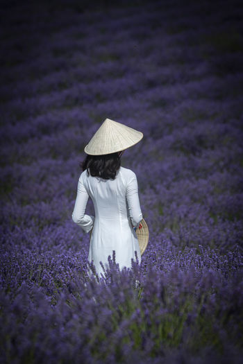 Rear View Of Woman Wearing Asian Style Conical Hat While Standing Amidst Flowering Plants On Field