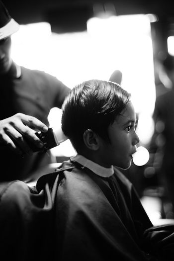 Barber cutting hair of boy at barber shop