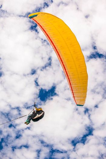 Low angle view of man paragliding against sky