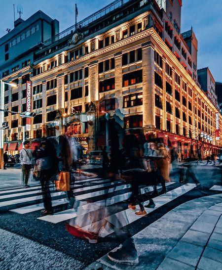 People walking on city street amidst buildings at dusk