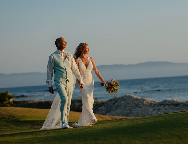 Side  view of bride and groom standing by sea against sky