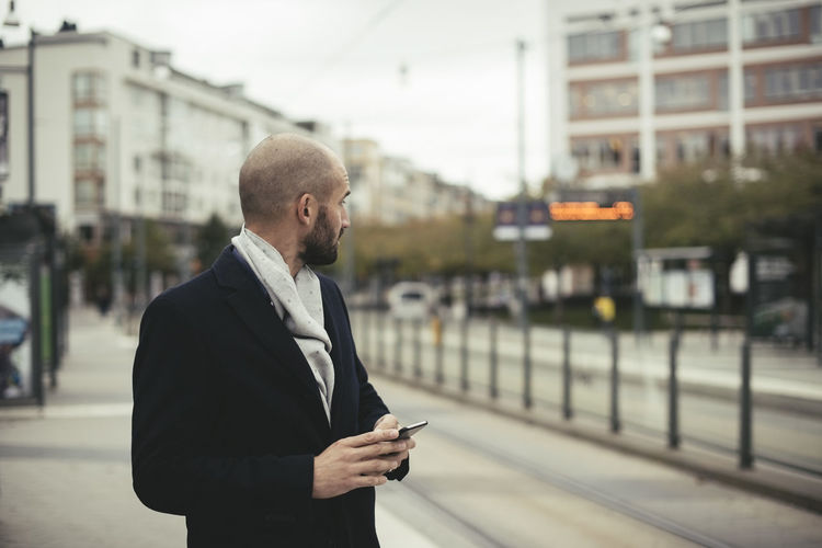 Man using mobile phone in city