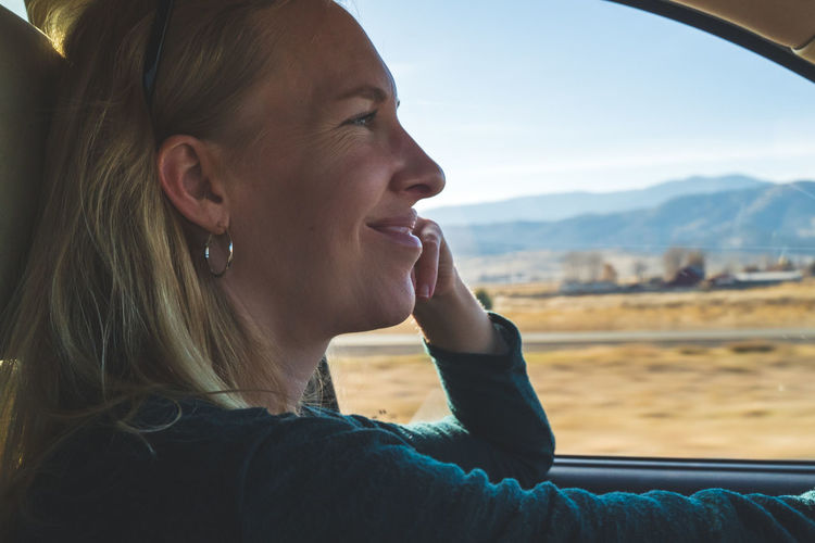 Smiling woman driving on road trip in desert with view out of drivers window.
