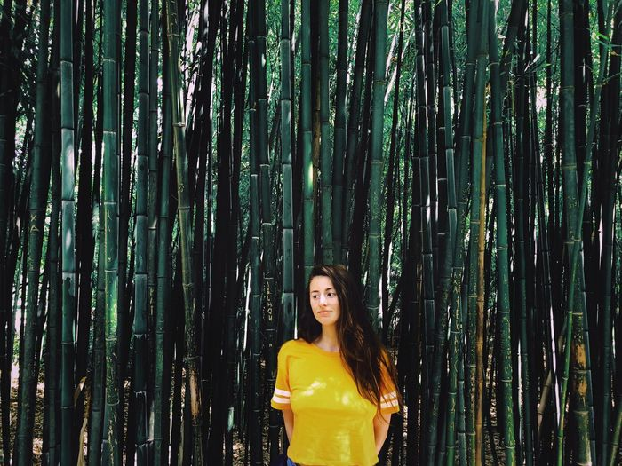 Thoughtful young woman standing against bamboo