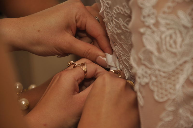 Cropped image of bridesmaids helping bride to dressing