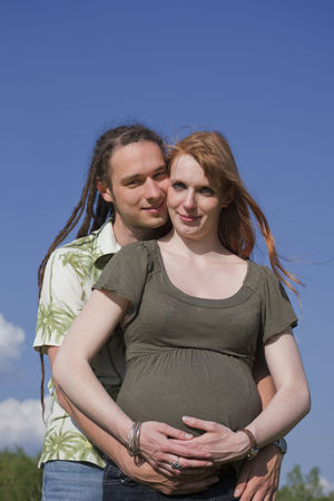 Young Couple awaiting a Baby – Germany, Europe Affectionate Anticipation Beginnings Blue Sky Bonding Change Couple Dreadlocks Embracing Happiness Heterosexual Couple Life Events Lifestyles Long Hair Love New Life Outdoors Parenthood Parents Portrait Pregnant Togetherness Two People Waist Up Young Couple