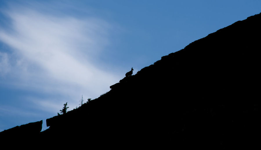 Low angle view of silhouette rocks against sky