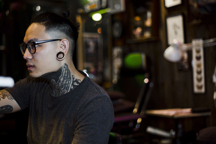 Side portrait of young Thai Asian tattooist neck inked and ear lobe gauging at MORNIKK tattoo studio Srinakarin Rd Bangkok Thailand Barbershop Business Hands Piercing Profile Stylish Tattooed Working Young Entrepreneur Body Modification Close Up Creative Ear Lobe Eyeglasses  Face Mood Neck One Person Portrait Real People Selective Focus Skin Tattoo Young Adult Hipster