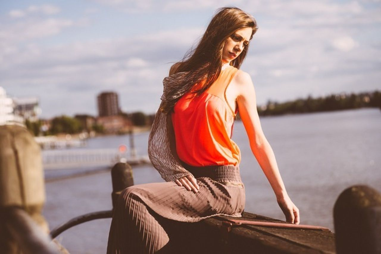 Beautiful woman sitting on retaining wall by river against sky