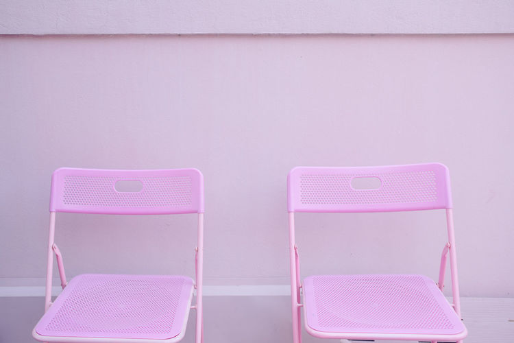 Empty chairs against wall