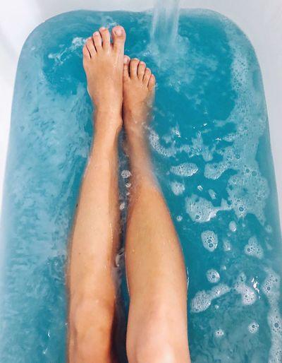 Low section of woman legs sitting in bathtub