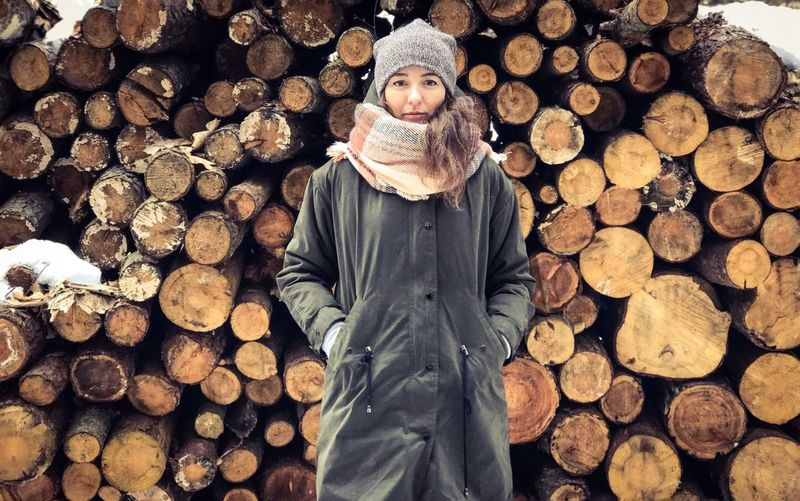 Portrait of woman with hands in pockets standing against logs during winter
