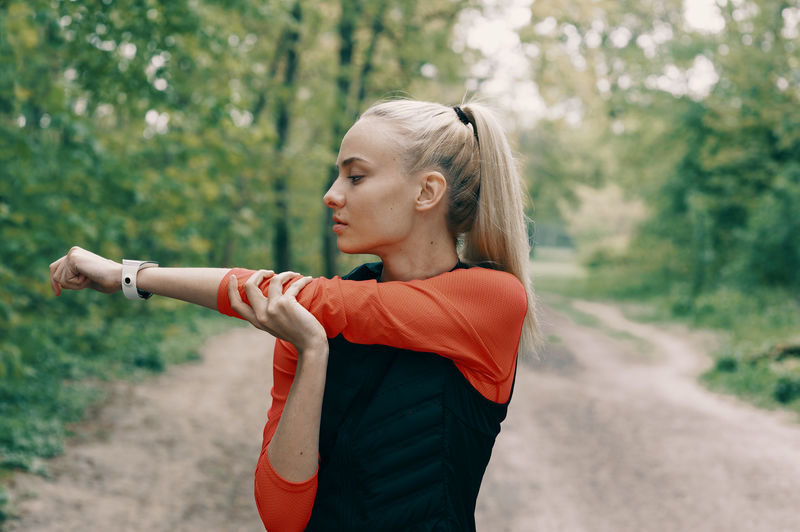 Close-up of young woman stretching at park