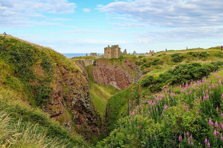 Distant View Of Dunnottar Castle Over Green Landscape Against Sky