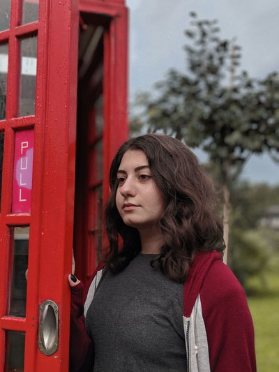 Young woman looking away while standing by telephone booth