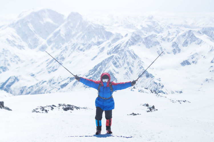 Man with ski poles standing on snow against snowcapped mountains