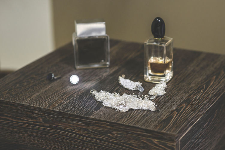 High angle view of jewelry with perfume spray on wooden table