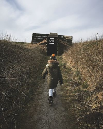 Rear view of kid walking on field against sky