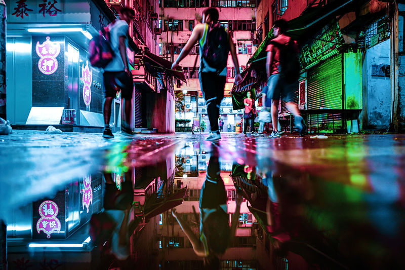 People standing in illuminated city at night