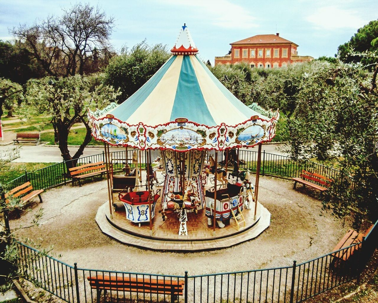 amusement park, arts culture and entertainment, carousel, amusement park ride, tree, outdoors, merry-go-round, leisure activity, day, no people, park - man made space, carousel horses, water, sky