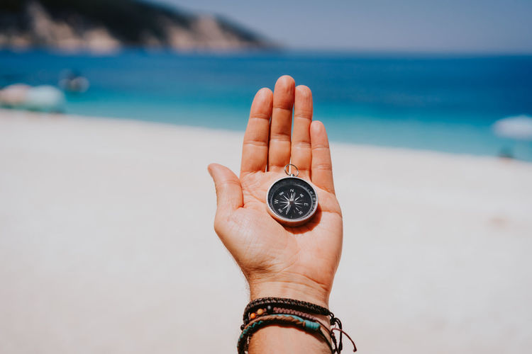 Midsection of person holding compass at beach