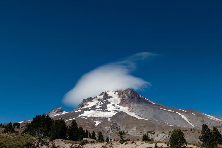Low angle view of mount hood against blue sky and cloud formation