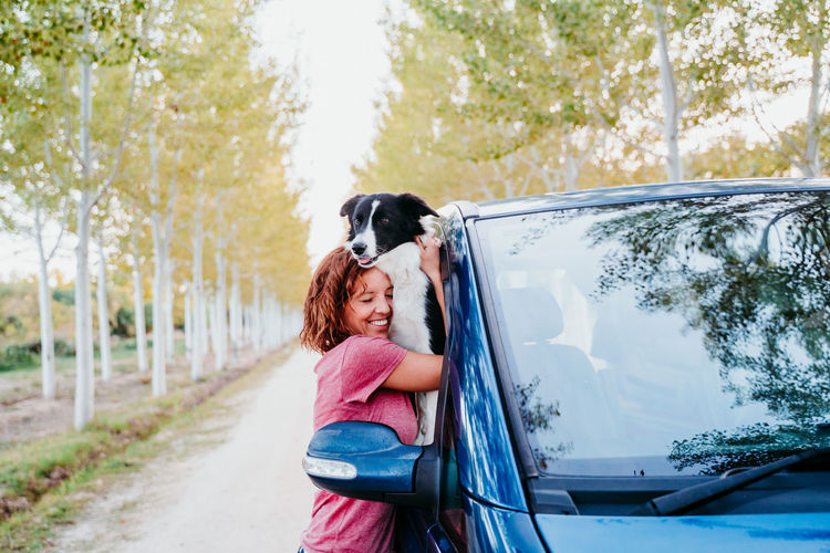 Side view of woman embracing dog through car window