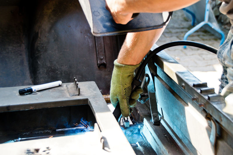 Cropped hand of male welder welding vehicle