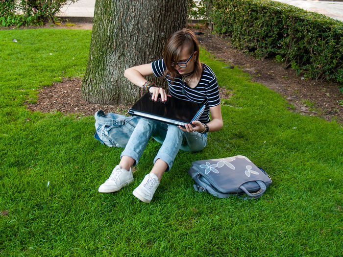 Teenage girl using laptop while sitting on grassy field