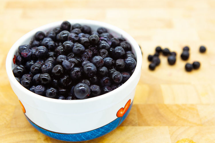Blueberries in a rounded bowl on a wooden table