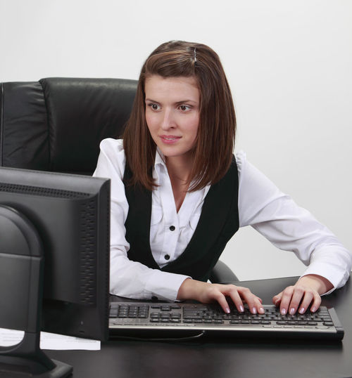 Young woman working on a computer. Computer Technology Furniture One Person Office Business Indoors  Business Person Businesswoman Adult Front View Sitting Desk Young Adult Using Computer Workplace Desktop Desktop Pc Keyboard Typing On Keyboard