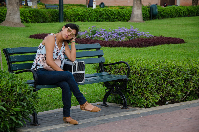 Girl with sunglasses on a park bench waiting Girl Waiting Park Bench Bad Sad Woman Young Women Beautiful Brunette Nature Phone Sitting Boyfriend Street Date Background Portrait Alone Teenager Style Relaxation Leisure Activity Grass One Person