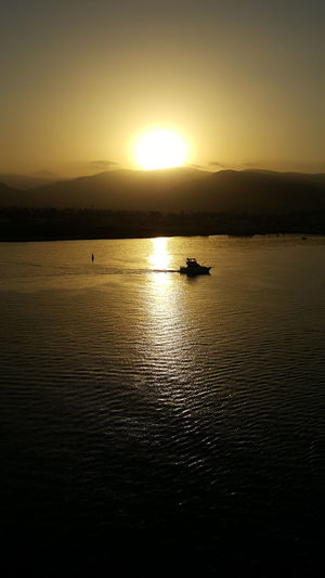 Sunset Reflection Scenics Sun Water Nature Silhouette Tranquility Tranquil Scene Sky No People Beauty In Nature Travel Destinations Sunlight Nautical Vessel Outdoors Sea Landscape