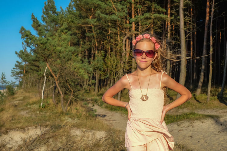 Portrait of girl wearing sunglasses while standing against trees during sunset