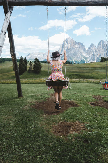 One Person Full Length Grass Real People Plant Field Land Nature Rear View Lifestyles Leisure Activity Women Day Sky Casual Clothing Tree Swing Girls Beauty In Nature Outdoors Human Arm Dolomiti Seiseralm Woman Hat This Is Natural Beauty A New Perspective On Life