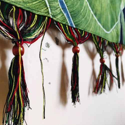 Close-up of curtain tassels against wall