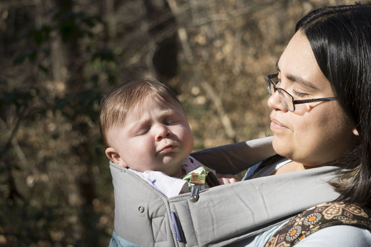 Mother with cute baby boy in sling