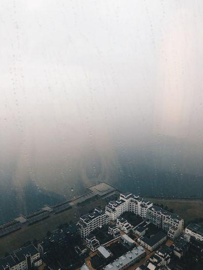Aerial view of city buildings seen through wet window