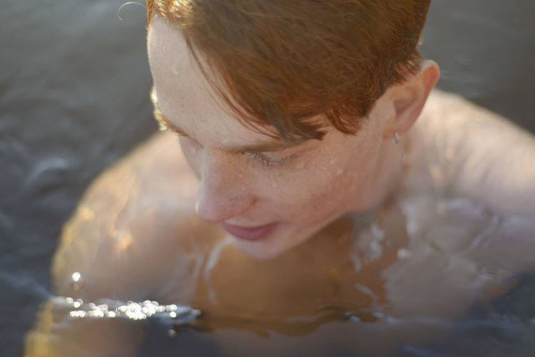 Close-up portrait of shirtless man swimming in pool